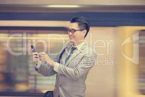 Businessman texting at subway.