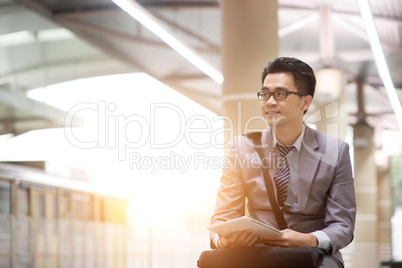 Businessman using tablet pc at train station.