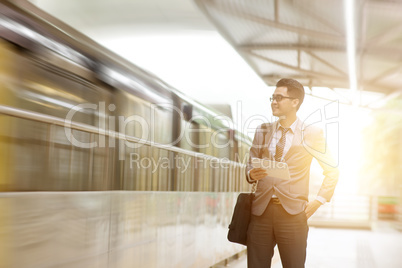 Businessman using tablet pc while waiting train.