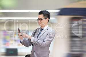 Businessman using smartphone at subway.