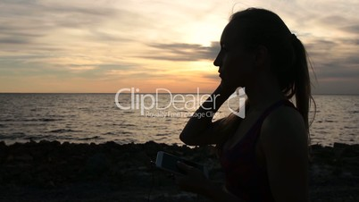 Runner woman setting music on smartphone at sunset