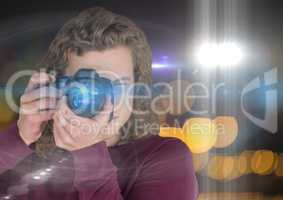 photographer man with long hair taking a photo (foreground). Blurred lights and flares behind and ov