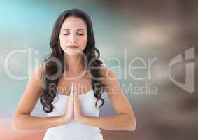 Woman meditating against blurry blue and brown background