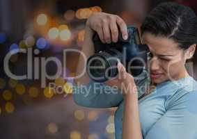 young photographer taking a photo. Blurred city lights at night behind