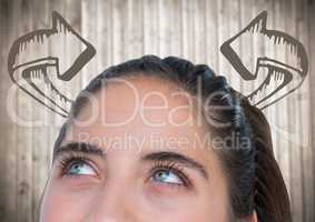 Top of woman's head looking at 3D curved arrows against blurry wood panel