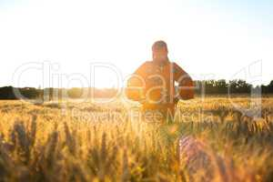 African woman in traditional clothes standing in a field of crop