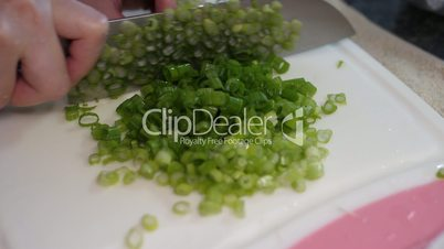 Slow motion of woman cutting green onion on cutting board