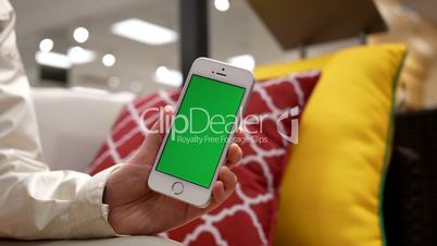 Motion of woman holding green screen mobile phone on sofa