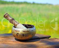 Copper Tibetan singing bowl on a brown wooden background, blurre