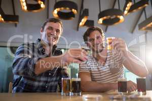 Portrait of happy friends holding beer glass