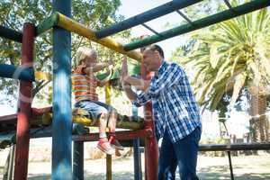 Happy father giving high five to son sititng on jungle gym