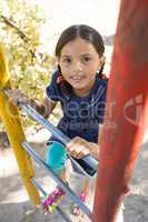 Portrait of happy girl climbing ladder of jungle gym