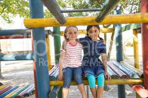 Portrait of smiling girls with arms around sitting on jungle gym