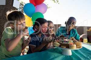 Happy children enjoying sweet food at park