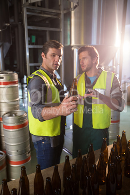Coworkers examining bottles at warehouse