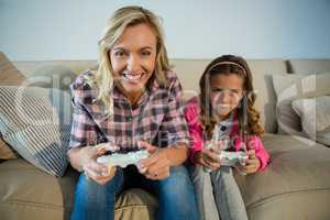 Mother and daughter playing video game in the living room
