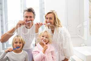 Family brushing teeth together in the bathroom
