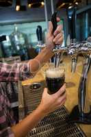 Cropped hands of barmaid pouring drink from tap in glass at counter
