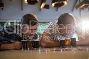 Male friends looking at beer glass at bar counter