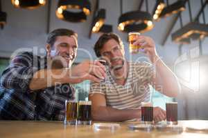 Smiling friends holding beer glass at bar counter