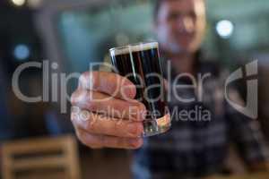 Close up of man holding beer glass at bar