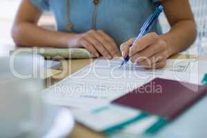 Female executive filling form at her desk