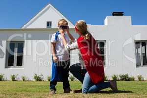 Mother and son pretending to be superhero in the backyard