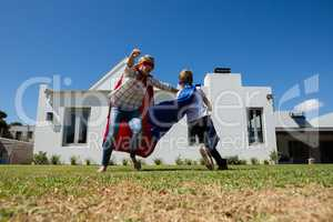 Mother and son in superhero costume playing in the backyard
