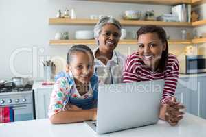 Happy family standing near kitchen worktop with laptop