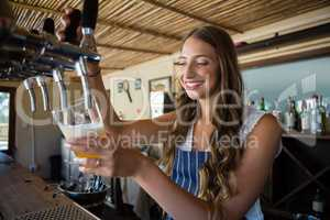 Happy barmaid pouring beer from tap in glass