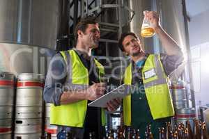 Coworkers examining beer in beaker