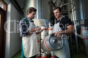 Workers examining kegs