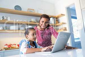 Mother and daughter using laptop in kitchen worktop