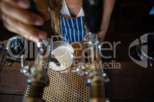 Midsection of barmaid pouring beer from tap in glass