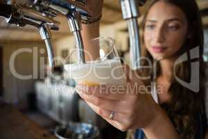 Close-up of barmaid pouring beer from tap in glass