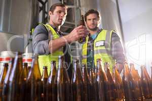 Coworkers examining beer bottles