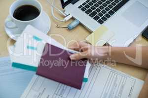 Female executive holding tickets and passport at her desk