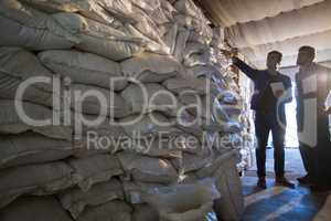 Coworkers examining barley sacks