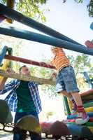 Happy father looking at son walking on jungle gym at playground
