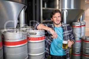 smiling male worker holding beer glass while standing at factory
