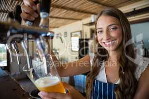 Portrait of smiling barmaid pouring beer from tap in glass