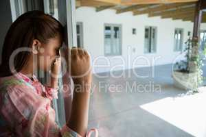 Woman leaning on window at home