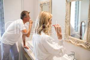 Couple brushing teeth in front of mirror