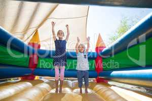 Portrait of happy siblings with arms raised jumping on bouncy castle
