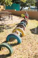Children playing by tyres at playground during sunny day