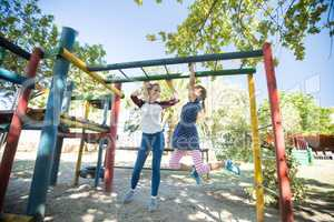 Happy mother talking to daughter hanging on jungle gym
