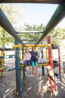Portrait of smiling girls sitting on jungle gym