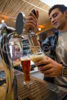 Young bartender pouring drink from tap in glass
