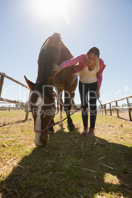 Full length of woman bending by horse on field