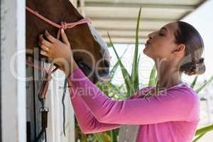 Young woman touching horse